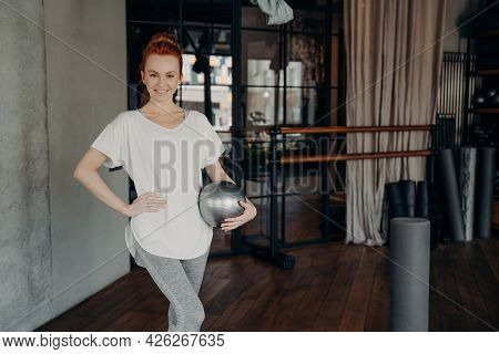 Young Smiling Pilates Instructor With Ginger Hair Standing In Fitness Studio Or Gym With Her Hand On