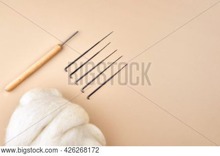 Needles And Skein Of Wool For Felting On A Beige Background, Copy Space, Top View.