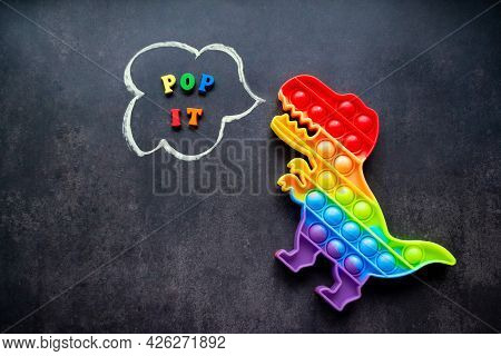 Pop It Dinosaur Toy Rainbow Colors On A Black Background With Multicolored Letters And The Inscripti