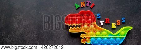 Banner With Toy Pop It Dinosaur Rainbow Colors On A Black Background With Multicolored Letters And T