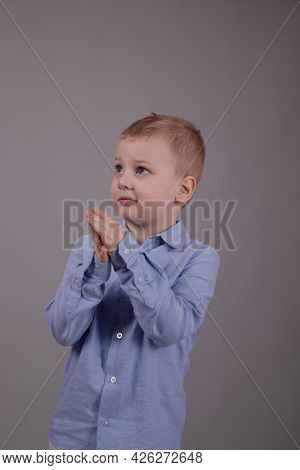 Charming Little Preschool Boy In White Pants And Blue Shirt On Gray Background. Child, Kid.