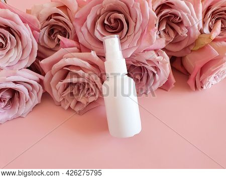 Unbranded White Cosmetics Spray Bottle And A Lot Of Pink Roses On Pink Background. Mockup. Skincare