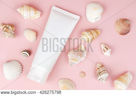Unbranded White Squeeze Bottle Cosmetic Tube And A Lot Of Different Sea Shells On Pink Background. N