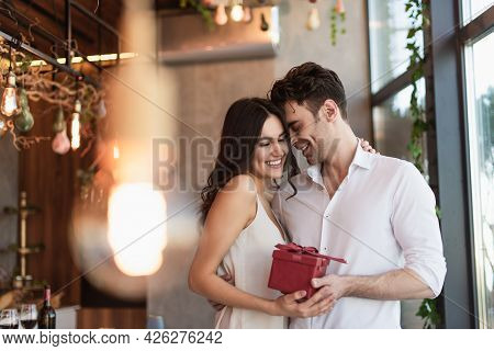 Joyful Man Holding Red Gift Box Near Smiling Girlfriend In Slip Dress In Restaurant
