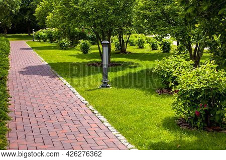 Straight Stone Tile Pavement In A Park Landscaped With Green Grass And Bushes With Tree Bark Mulchin