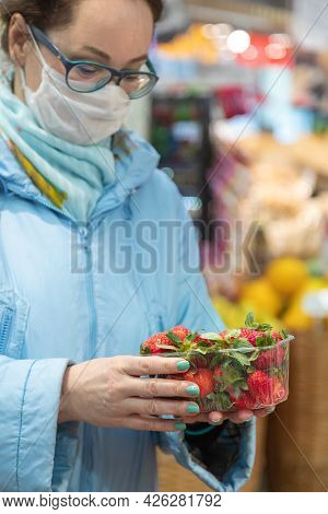 24.04.2021, Russia, Moscow. Caucasian Woman Chooses Fresh Strawberries In The Supermarket. In The Ha