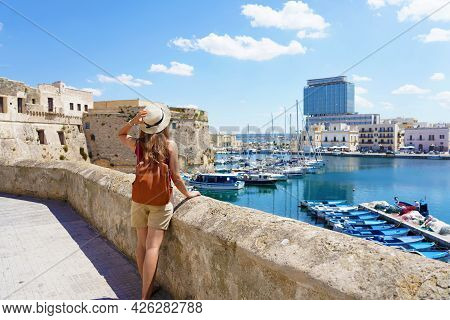 Summer Holiday In Italy. Back View Of Young Woman With Hat And Backpack In Gallipoli Old Town, Salen