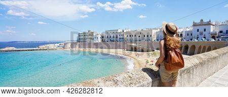 Traveling In Italy. Panoramic View Of Female Backpacker With Hat In Gallipoli Village, Salento, Ital