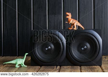 Two-way Speaker System Next To Toy Dinosaurs On A Background Of Natural Pine Boards. An Example Of I