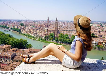 Beautiful Young Woman With Hat Sitting On Wall Looking At Stunning Panoramic View Of Verona City Wit