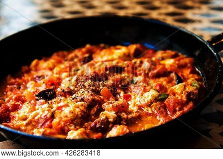 Traditional greek recipe made with octopus, feta cheese and boiled tomatoes cooked in a vintage pan for a mediterranean meal