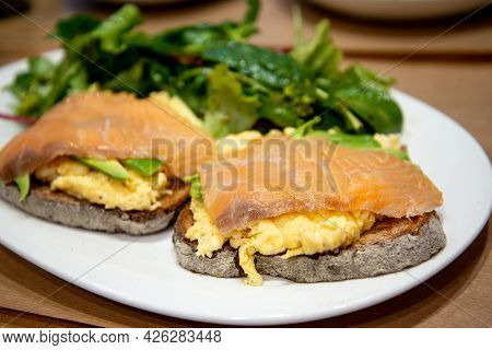 Scrambled eggs with fresh avocado and salmon served on two toasts  wheat bread with fresh lettuce on white plate for a healthy breakfast