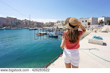 Visit Italy. Rear View Of Young Female Tourist Holding Hat And Looking Giovinazzo Harbor In Apulia,