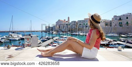 Holidays In Italy. Back View Of Beautiful Girl Sitting On Wall Enjoying View Of Giovinazzo Harbour I