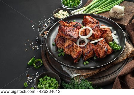 Delicious, Fried Meat With Onions On A Black Background With Herbs, Sauces And Spices. Side View, Sp