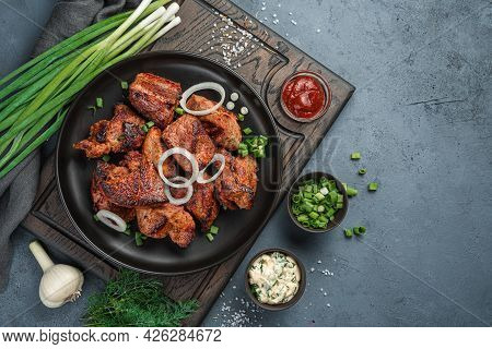 Fried Meat With Green Onions, Dill And Sauces On A Cutting Board On A Dark Gray Background. Top View