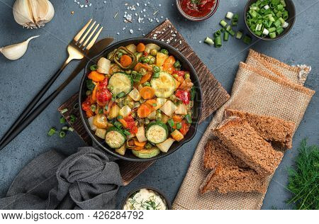 Vegetable Stew, Rye Bread And Greens On A Gray-blue Background. Top View, Close-up.
