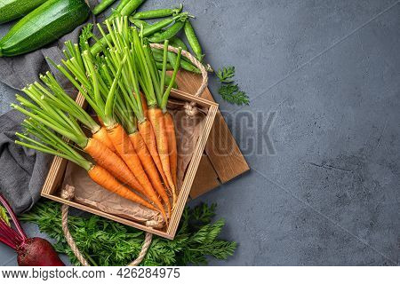 Young Carrots In A Wooden Box, Zucchini And Beetroot On A Blue-gray Background. Top View, Copy Space