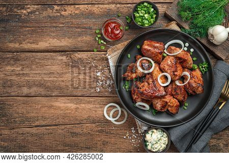 A Plate Of Fried Meat With Onions And Fresh Herbs On A Wooden Background. Kebab, Barbecue. Top View,