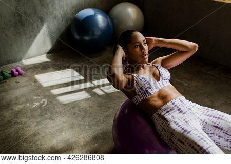 Sportive woman doing the sit-ups on a balance ball