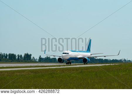 Passenger Plane Rides On The Runway At The Airport.