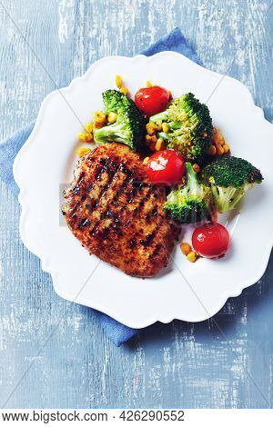 Grilled Turkey Breast With Oven Baked Broccoli, Cherry Tomatoes And Sweet Corn. Bright  Wooden Backg