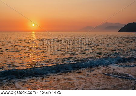 Beautiful Landscape - Beach On Sunset -red And Orange Sky And Sunlight Reflecting On Sea Water.