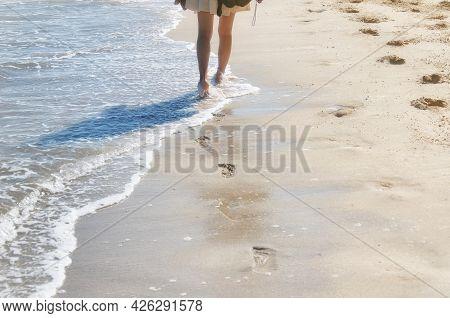 A Woman Wearing A Dress Walking Barefoot On Long Beach In Batu Ferringhi Penang Malaysia.