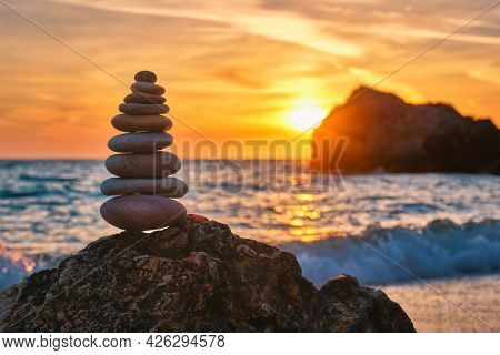 Concept of balance and harmony. Cairn stack of stones pebbles cairn on the beach coast of the sea in the nature on sunset. Meditative art of stone stacking