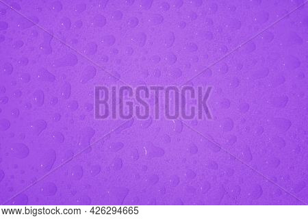 Top View Of Vibrant Purple Colored Water Droplets On The Tabletop