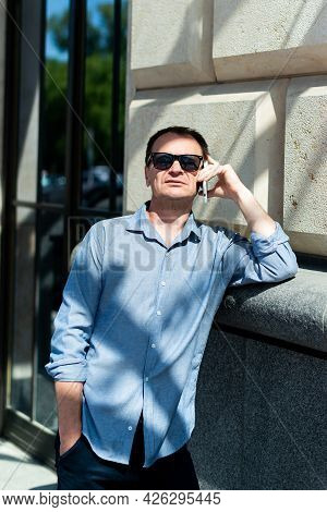 Caucasian Man Forty Years Old Businessman Near The Building Talking On The Phone.