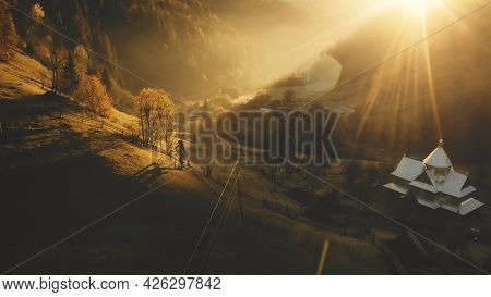 Sunset over fir mountain forest aerial. Autumn nature landscape. Rural cottages at sunny mount valley. Countryside vacation at unbelievable Carpathians village in sun light. Cinematic Ukraine, Europe