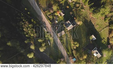Top down village at mountain valley aerial. Autumn nature landscape. Cottages at rural road. Colorful leafy and pine forest. Cinematic vacation at Carpathian countryside, Ukraine, Europe