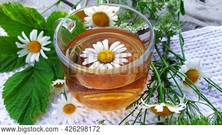 Chamomile Drink. Tea With Chamomile Flowers. Flowers And A Cup With Tea On A Wooden Background.