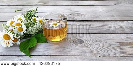 Chamomile Tea And A Bouquet Of Chamomiles. Cup With Tea On A Wooden Background.