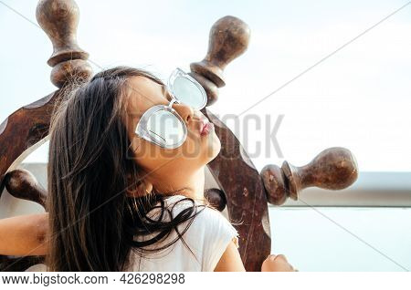 Little Girl Playing To Be A Sailor On A Balcony With A Boat Rudder And The Background Of The Sea.