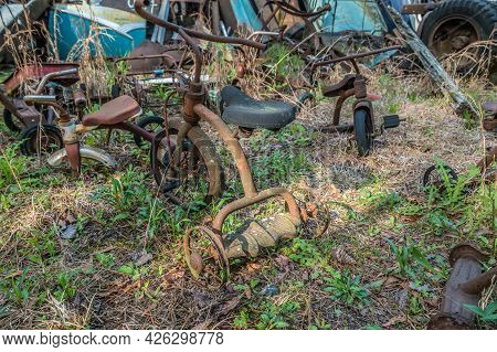 Several Kinds Of Broken And Rusted Vintage Tricycles Discarded Together In A Junkyard Left To Rot An