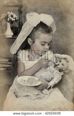 Little Girl Is Feeding Her Doll