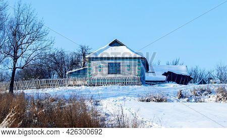 Old Village House In Winter In Sunny Weather. The Village In Winter