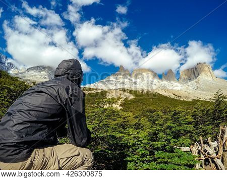 Man From Behind, Sitting On A Stone Looking At The Clear Mountains, Torres Del Paine.