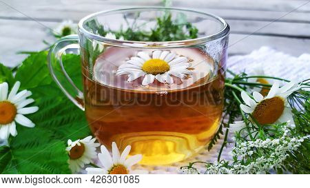 Chamomile Tea. Flowers And A Cup With Tea On A Wooden Background. Drink With Chamomile Flowers.
