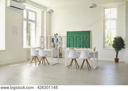 Modern Empty Classroom Interior With Desks, Chairs And Chalkboard. Light Schoolroom With Comfy Furni