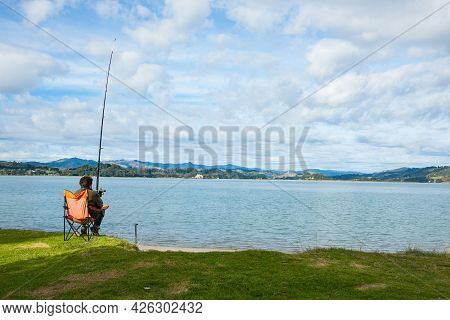 Whakatane New Zealand - May 26 2012; Lone Fisher At Ohiwa Harbour Rear View Patiently And Hopefully