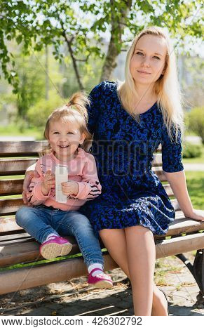 A Young Beautiful Pregnant Woman And A Little Toddler Daughter Are Sitting On A Park Bench. A Sunny