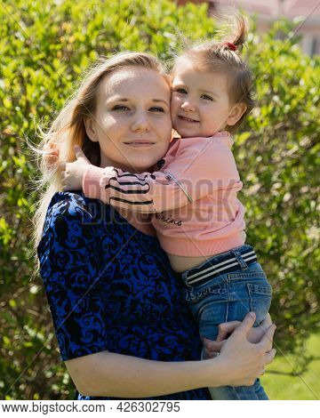 A Little Toddler Girl Hugs Her Young Beautiful Mother. A Sunny Day. The Happiness Of Motherhood