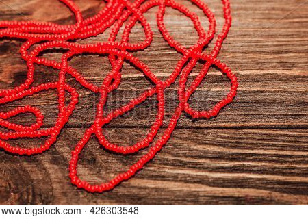Red Beads On A Wooden Background. Beads And Handicrafts For Creativity.