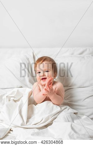 Redhead Toddler On Bed Smiles. Infant Development Concept, Toddler Restful Sleep, Teething, Colic.