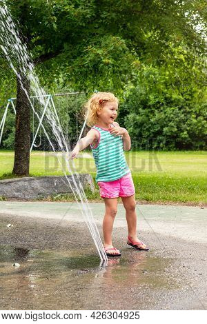 Little Smiling Child Playing At Water Splash Pad Fountain In Park Playground On Hot Summer Day.