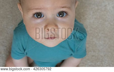 Portrait Of A Sweet Little Baby Boy Looking Up With Beautiful And Innocent Eyes