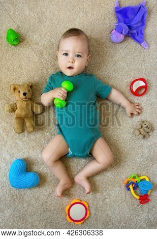 Happy Sweet Little Baby Boy On The Floor With Colorful Toys, Top View